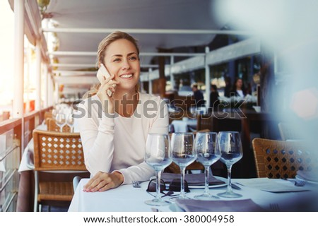 Young hipster girl having cheerful conversation on cell telephone during lunch in sidewalk cafe, attractive smiling female tourist speaking on mobile phone while resting in restaurant after strolling - stock photo