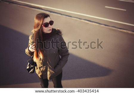 Young hipster girl in grey park coat, sunglasses and marsala scarf posing outdoors at day. Attractive young model and trendy youth fashion - stock photo