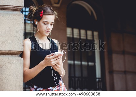 Young hipster girl is standing in front of a monumental building with smart phone and earphones in her ears.
