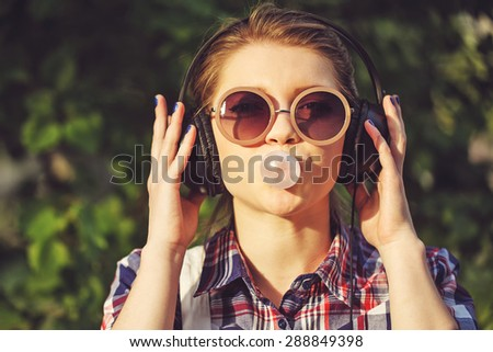 Young hipster girl listening to music on headphones in a summer park. Portrait close-up with chewing gum. Warm toning. The concept of cheerful youth. - stock photo