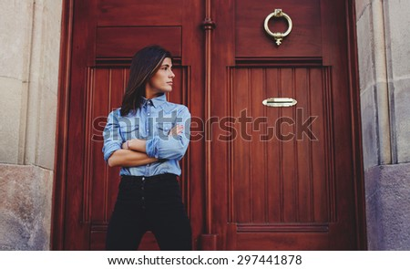 Young hipster girl posing for the camera on a background of brown wooden door with copy space for your text message or content,confident stylish woman looks to the side while standing in urban setting - stock photo