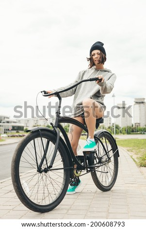 Young hipster girl riding on black bike. Outdoor lifestyle portrait