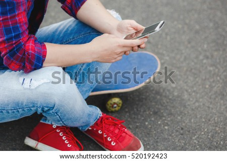 Young hipster girl sitting at skate park and chatting on her phone