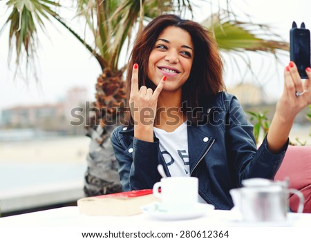 Young hipster girl taking self portrait with phone camera doing sign of the horns or rock hand gesture, afro american woman having fun while photographing herself with smart phone in coffee shop - stock photo