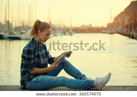 Young hipster girl using touch pad while sitting against sea port background with copy space for your content, attractive woman watching movie on digital tablet while rest after walking outdoors  - stock photo
