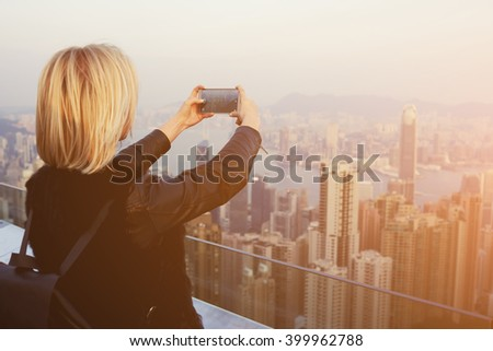 Young hipster girl with a rucksack on back is shooting video on mobile phone of an amazing view of New York. Blonde female traveler is making photo with cell telephone camera of China landscape - stock photo