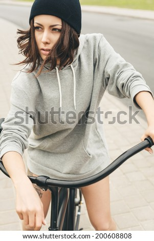 Young hipster girl with black bike. Outdoor lifestyle portrait
