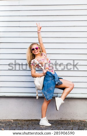 Young hipster girl with sunglasses dressed in shorts and a T-shirt posing in the white wall. Happy blond woman with a backpack standing on the background wall - stock photo