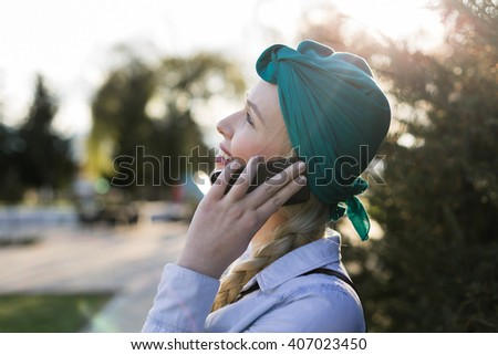 Young hipster girl with trendy look chatting on smart phone while resting in park in spring day, stylish female student searching information in network while sitting at the campus during class break