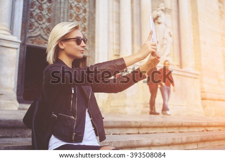 Young hipster girl with trendy look is shooting video on portable touch pad of a street view during her travel abroad. Charming woman is photographing herself with front camera of digital tablet  - stock photo