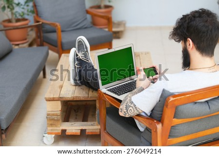 young hipster guy using a laptop and a smart phone.focus on the phone - stock photo