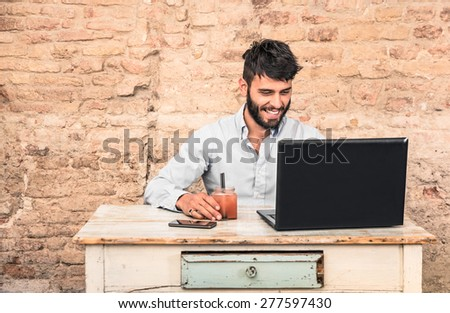 Young hipster guy with mustache sitting at vintage desk with laptop computer in grunge alternative office - Concept of start up business enjoying working hours - Soft retro desaturated filtered look - stock photo
