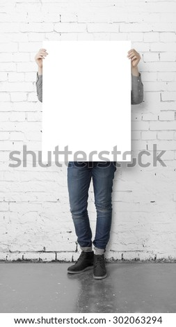 young hipster holding poster in brick room - stock photo