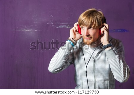 Young hipster listening to music on red headphones