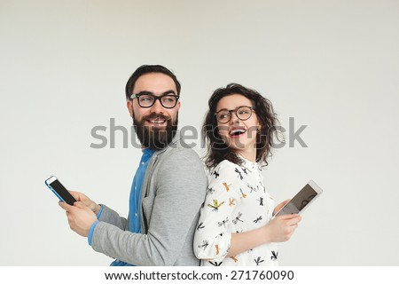 Young hipster man and woman in glasses with smartphone and tablet isolated on the blank white background - stock photo