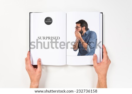 Young hipster man doing surprise gesture printed on book - stock photo