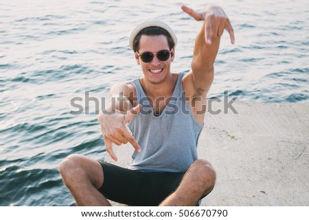 Young hipster man in glasses having fun