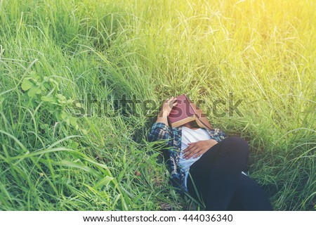 Young hipster man lying down on grassland napping tired after reading book with nature around. - stock photo