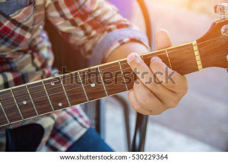 Young hipster man playing guitar to relaxing on his holiday, enjoy with natural and fresh air.