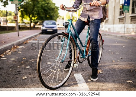 Young hipster man riding a bicycle in the city. Depth of field - stock photo