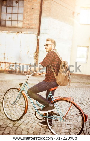Young hipster man riding vintage bike on city street - stock photo
