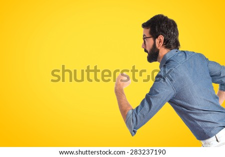 Young hipster man running fast over colorful background
