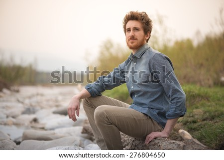 Young hipster man sitting on rocks next to a river and looking away, nature and healthy lifestyle concept - stock photo