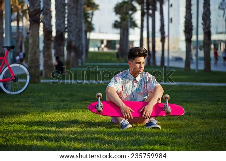 Young hipster man sitting on the grass with longboard, stylish teenager man seated near palm trees looking away, leisure time at sunset, urban culture - stock photo