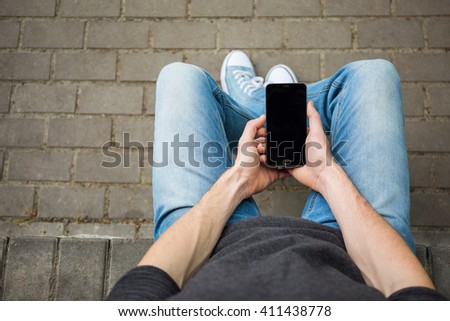 Young hipster man sitting outdoors using his smartphone