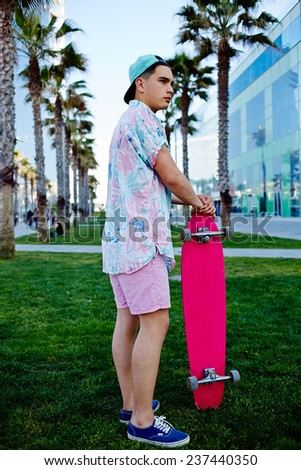 Young hipster man standing on the grass holding his longboard, stylish teenager man stand in california beach palm trees park looking away, leisure time at holidays, urban culture and youth - stock photo
