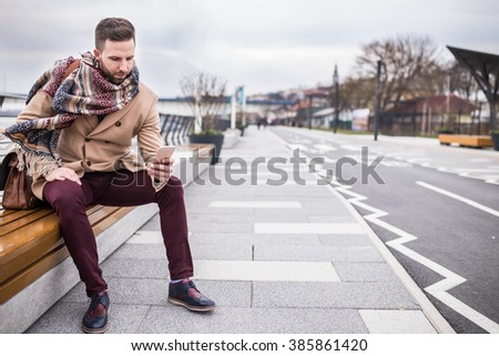 Young hipster man texting his girlfriend while waiting for her at bench - stock photo