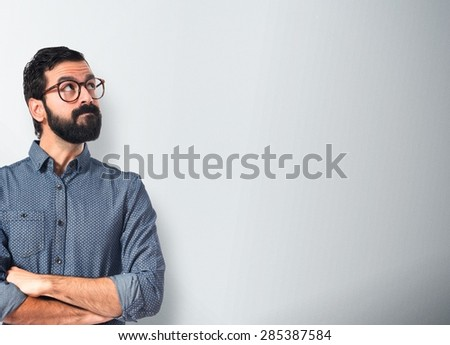Young hipster man thinking over textured background