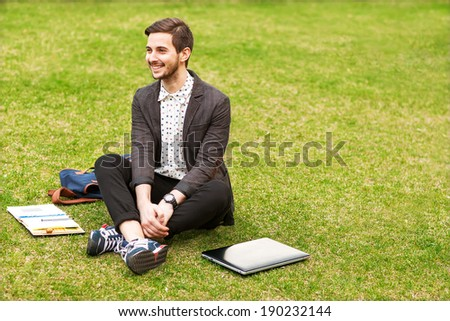 Young hipster man using his laptop on the grass and makes notes in a notebook