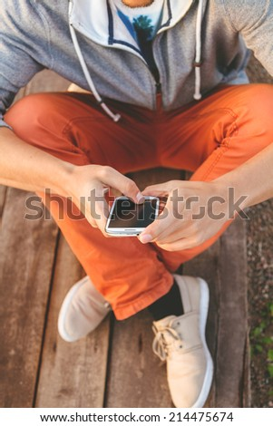 Young  hipster man using smart phone sitting on wooden boards - stock photo