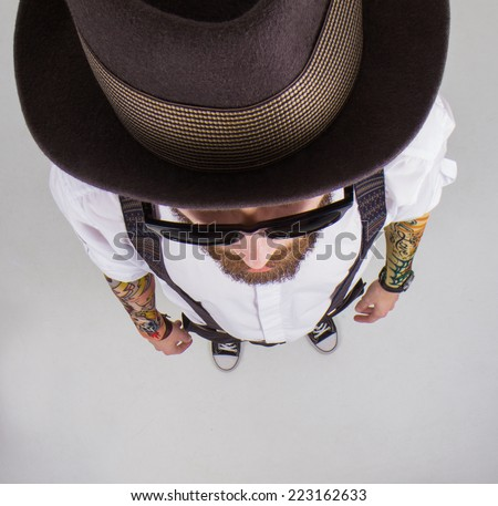 young hipster man wearing  hat and bow-tie and a funny tattoo