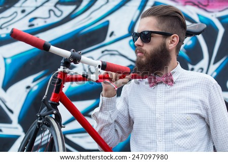 Young hipster man with a bike posing near a wall full of graffiti. - stock photo