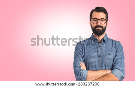 Young hipster man with his arms crossed over colorful background