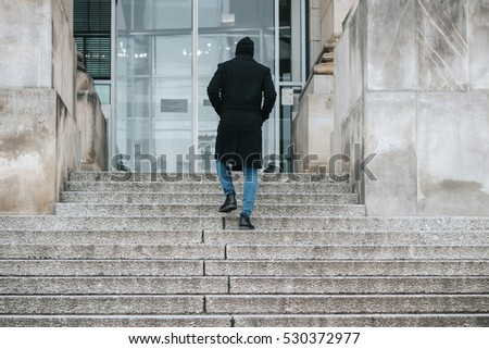 Young hipster man with long winter coat climbing stone stairs to the big building modern entrance - subject shot from the back with no visible face, anonymous