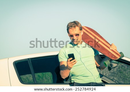 Young hipster man with smartphone listening music during trip break next his car - Concept of new trends and modern technologies mixed with a retro lifestyle - Soft desaturated vintage filtered look - stock photo