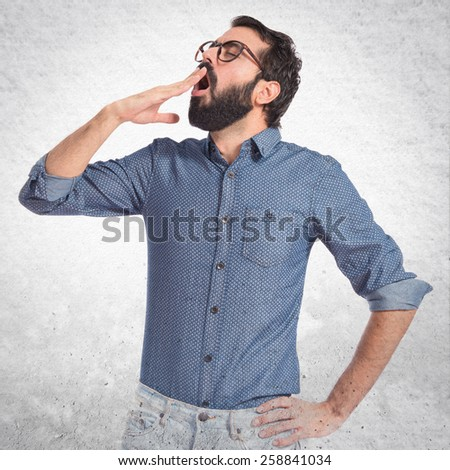 Young hipster man yawning over textured background  - stock photo