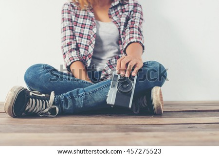 Young hipster photographer hand holding retro camera sitting on wooden floor.