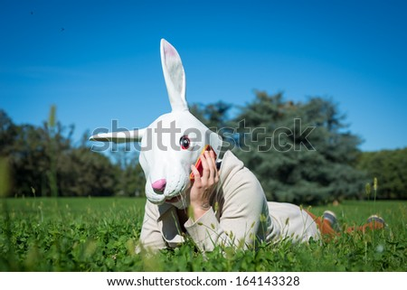 young hipster rabbit mask woman on the phone in autumn on the grass - stock photo