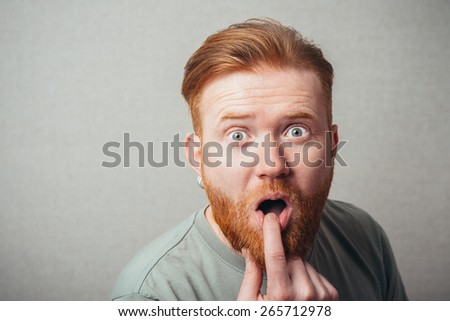 Young hipster red bearded Man finger in mouth - stock photo