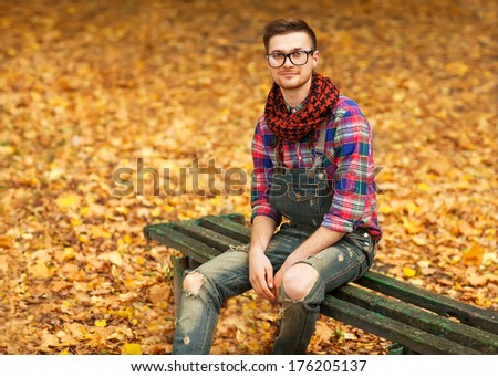 Young hipster relaxed man in nature, back on tree, meadow behind
