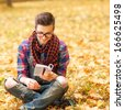 Young hipster relaxed man reading book in nature, back on tree, meadow behind - stock photo