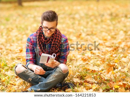 Young hipster relaxed man reading book in nature, back on tree, meadow behind