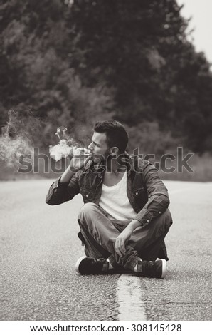 Young hipster sitting on the road and smoking a cigarette near forest. Vintage BW Instagram style effect, soft and selective focus, shallow DOF, low light, grain texture visible on maximum size - stock photo