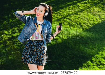 young hipster stylish beautiful girl listening to music, mobile phone,headphones, enjoying, denim outfit, smiling, happy, cool accessories, vintage style, having fun, laughing, park - stock photo