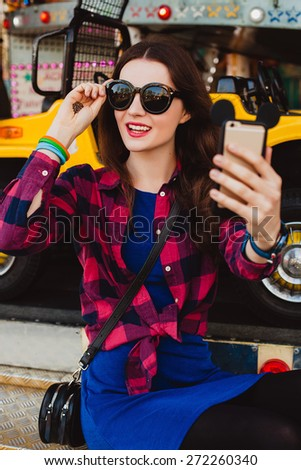 young hipster stylish beautiful woman in sunglasses making selfie on her mobile phone  dressed in blue dress and checkered shirt at the amusement park, enjoying the summer day, cool accessories