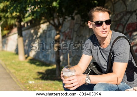 Young hipster stylish man with sunglasses holding smoothie with a straw. Sitting on a bench on a sunny afternoon